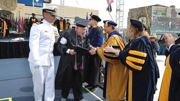 """World War II veteran Bob Barger, assisted by Haraz Ghanbari, University of Toledo director of military and veteran affairs, greets school officials at the commencement ceremony at the University of Toledo, Saturday, May 5, 2018, in Toledo, Ohio. Now, 68 years since he last sat in a classroom, Barger graduated after a review of his transcripts from the late 1940s showed he completed enough courses to qualify for an associate's degree — a two-year diploma not offered when he was still in school. """"It was something I never dreamed of,"""" the 96-year-old Barger said. """"I knew I couldn't go back to school now. The university took a look at Barger's old school records because of a friendship he struck up with Ghanbari. (AP Photo/Carlos Osorio)"""