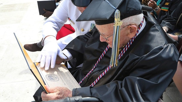"""World War II veteran Bob Barger, assisted by Haraz Ghanbari, University of Toledo director of military and veteran affairs, left, looks over his diploma at the commencement ceremony at the university, Saturday, May 5, 2018, in Toledo, Ohio. Now, 68 years since he last sat in a classroom, Barger graduated after a review of his transcripts from the late 1940s showed he completed enough courses to qualify for an associate's degree — a two-year diploma not offered when he was still in school. """"It was something I never dreamed of,"""" the 96-year-old Barger said. """"I knew I couldn't go back to school now. The university took a look at Barger's old school records because of a friendship he struck up with Ghanbari. (AP Photo/Carlos Osorio)"""