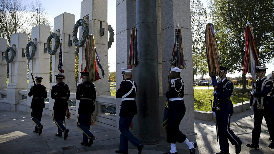 A U.S. military honor guard carries in the colors at the National World War II Memorial in Washington on Veteran's Day to pay tribute to the more than 16 million men and women who served with U.S. armed forces during World War II, Nov. 11, 2015.
