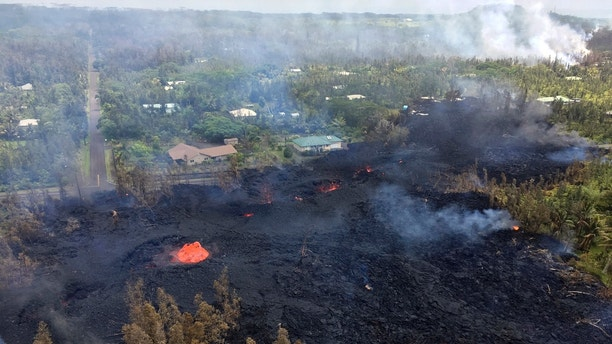 This Saturday, May 5, 2018, photo provided by the U.S. Geological Survey, shows Fissure 7 in Pahoa, Hawaii. At the peak of its activity, large bubble bursts occurred at one spot, lower left, in the fissure while spattering was present in other portions. The number of homes destroyed by lava shooting out of openings in the ground created by Hawaii's Kilauea volcano climbed to nine on Sunday, May 6, as some of the more than 1,700 people who evacuated prepared for the possibility they may not return for quite some time. (U.S. Geological Survey via AP)