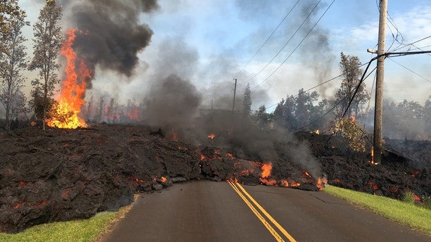 Lava advances along a street near a fissure in Leilani Estates, on Kilauea Volcano's lower East Rift Zone, Hawaii, the U.S., May 5, 2018. U.S. Geological Survey/Handout via REUTERS   THIS IMAGE HAS BEEN SUPPLIED BY A THIRD PARTY. IT IS DISTRIBUTED, EXACTLY AS RECEIVED BY REUTERS, AS A SERVICE TO CLIENTS     TPX IMAGES OF THE DAY - RC1C24B41D60