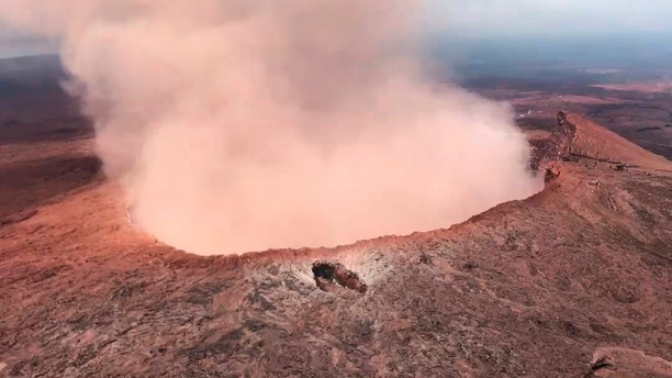 In this Saturday, May 5, 2018 photo provided by U.S. Rep. Tulsi Gabbard, who is on active duty Hawaii National Guard deployment, ash from the Puu Oo vent on Kilauea volcano rises into the air, near Pahoa, Hawaii. Hawaii's erupting Kilauea volcano has destroyed homes and forced the evacuations of more than a thousand people. (U.S. Rep. Tusli Gabbard/National Guard via AP)