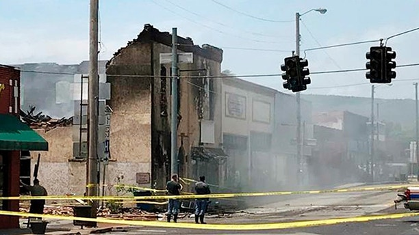 This photo from KHJBS/KHOG-TV shows the aftermath of a fire in downtown Talihina, Okla., Friday, May 11, 2018, that consumed several buildings. Four Oklahoma troopers were struck by gunfire or shrapnel while serving a drug-related warrant at a man's home that may have been booby-trapped to spark the large fire, authorities said. The suspect was shot and has been pronounced dead. (Courtesy KHBS/KHOG-TV via AP)