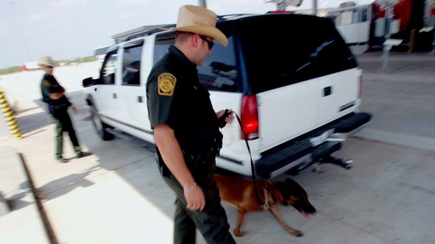 U.S. Border Patrol agents check a car's occupants (L) and use a dog to sniff out drugs (C) at a checkpoint coming into the U.S. outside Laredo, Texas May 4, 2006.  REUTERS/Rick Wilking - GM1DSNNJHSAA