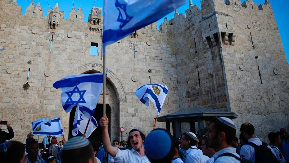 MAY 13: Israelis wave national flags outside the Old City's Damascus Gate, in Jerusalem