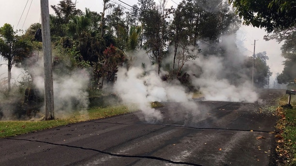 File - This May 7, 2018, file photo from the U.S. Geological Survey shows gas and steam rising from multiple fissures on Moku Street in the Leilani Estates Subdivision near Pahoa on the island of Hawaii. The lava hisses, crackles and pops. It roars like an engine as it sloshes and bubbles. It shoots into the sky, bright orange and full of danger, or oozes along the pavement, a giant bubbling blob of black marshmallow-like fluff, crushing homes and making roads impassable. (U.S. Geological Survey via AP, File)