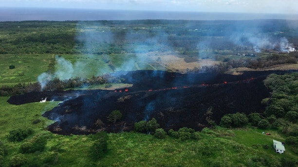 In this May 13, 2018 photo released by the U.S. Geological Survey, gases rise from a fissure near Pahoa, Hawaii. The new fissure in Hawaii's Puna District sent gases and lava exploding into the air, spurring officials to call for more evacuations as residents waited for a possible major eruption at Kilauea volcano's summit. (U.S. Geological Survey via AP)