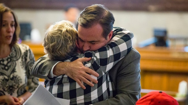 In a Tuesday, April 17, 2018 photo, Cincinatti Mayor John Cranley hugs a member of Kyle Plush's family before council's Law and Public Safety Committee meeting where Kyle Plush's death after he accidentally got pinned in the fold-away back seat of a minivan was discussed inside the Council Chambers at City Hall in Cincinnati. The teen's April 10 death has triggered long-overdue plans for upgrades at the city emergency center and helped force the city manager's resignation, and more changes could come after the Cincinnati police department's internal probe, the county prosecutor's investigation and vehicle safety reviews.  (Meg Vogel/The Cincinnati Enquirer via AP)