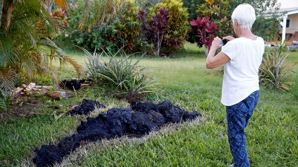 Patricia Spinoza, of Puna, takes a photo of lava on a lawn  on the outskirts of Pahoa during ongoing eruptions of the Kilauea Volcano in Hawaii, U.S., May 14, 2018.  REUTERS/Terray Sylvester - RC1569B446E0