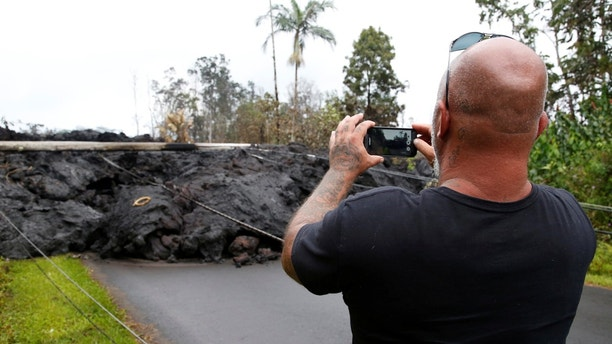 A resident of the Leilani Estates subdivision takes photos of a lava flow near his home during ongoing eruptions of the Kilauea Volcano, Hawaii, U.S., May 8, 2018.  REUTERS/Terray Sylvester - RC1EE7E7B2C0