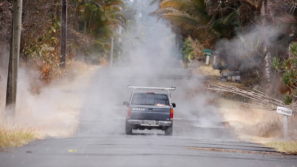 A driver steers through volcanic gasses in the Leilani Estates subdivision during ongoing eruptions of the Kilauea Volcano in Hawaii, U.S., May 13, 2018.  REUTERS/Terray Sylvester - RC1A06F9EF40