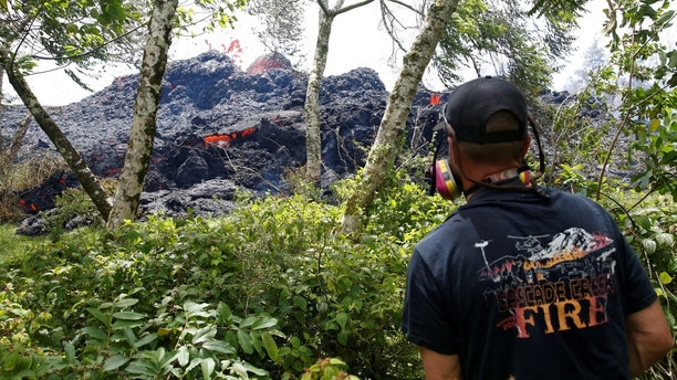 An onlooker watches as lava erupts from a fissure east of the Leilani Estates subdivision during ongoing eruptions of the Kilauea Volcano, U.S., May 12, 2018.  REUTERS/Terray Sylvester - RC17113DD4C0