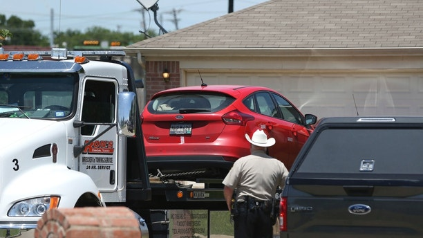 A vehicle is towed as Denton County Sheriff's officers investigate a crime scene at a home where multiple people were killed and one was hospitalized after a shooting at a home in the Remington Park neighborhood of Ponder Texas on Wednesday