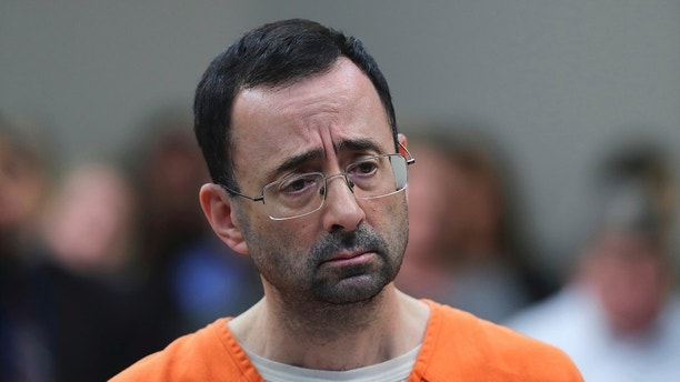 CORRECTS FROM CONVICTED TO SENTENCED - FILE - In this Nov. 22, 2017, file photo, Dr. Larry Nassar, 54, appears in court for a plea hearing in Lansing, Mich. Nassar was sentenced to decades in prison for sexually assaulting young athletes for years under the guise of medical treatment. (AP Photo/Paul Sancya, File)