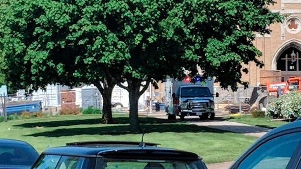An emergency vehicle appears outside Dixon High School Wednesday, May 16, 2018 in Dixon, Ill. Officials say a police officer has shot and wounded a gunman at a northern Illinois high school. The Dixon city manager Danny Langloss says police confronted a former male student with a gun on school property about 8 a.m. Wednesday. Langloss says the gunman shot at an officer who returned fire and hit him. He is in custody with what Langloss described as non-life-threatening injuries. (Rachel Rogers/Sauk Valley Media via AP)