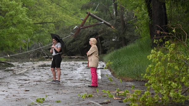 Two women look at the storm damage in Bridgewater, Conn.,  Tuesday, May 15, 2018. after severe storms rolled through the area.  Residents in the Northeast cleaned up Wednesday, a day after powerful storms pounded the region with torrential rain and marble-sized hail, leaving more then 200,000 homes and businesses without power.  (John Woike/Hartford Courant via AP)