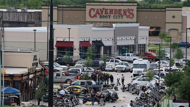 "FILE - In this May 17, 2015 file photo, authorities investigate a shooting in the parking lot of Twin Peaks restaurant in Waco, Texas. Prosecutors have dismissed another 42 cases relating to the 2015 shooting in Waco involving rival biker gangs that left nine dead and 20 others injured. McLennan County prosecutors said Tuesday, May 8, 2018, they're dismissing the cases while focusing on ""more culpable"" defendants. (AP Photo/Jerry Larson, File)"