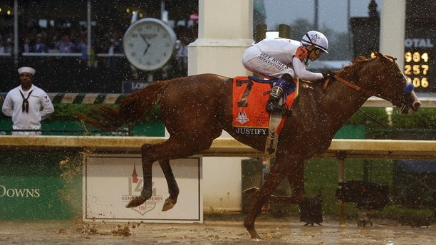 Mike Smith rides Justify to victory during the 144th running of the Kentucky Derby horse race at Churchill Downs Saturday, May 5, 2018, in Louisville, Ky. (AP Photo/Kiichiro Sato)