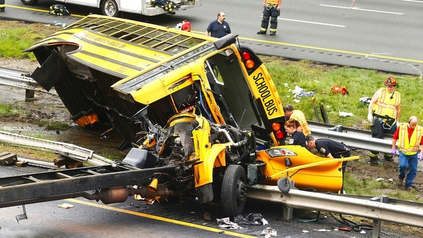 Emergency personnel examine a school bus after it collided with a dump truck, injuring multiple people, on Interstate 80 in Mount Olive, N.J., Thursday, May 17, 2018. (Bob Karp/The Daily Record via AP)