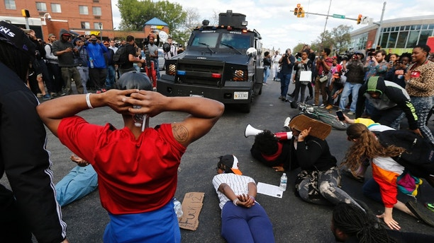 Members of the community lie down in the street, forcing a police armored vehicle to reverse back down the street in Baltimore, Maryland, April 28, 2015. Baltimore's mayor came under criticism on Tuesday for a slow police response to some of the worst urban violence in the United States in years in which shops were looted, buildings burned to the ground and 20 officers were injured. REUTERS/Jim Bourg - TB3EB4S1KPA4B