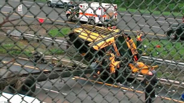 This image taken from WABC-TV video shows an overturned school bus after it collided with a dump truck, injuring multiple people, on Interstate 80 in Mount Olive, N.J., Thursday, May 17, 2018. (WABC-TV via AP)