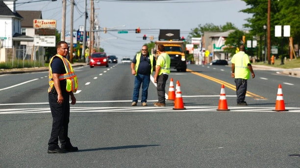 Officials guard a roadblock near a scene where a Baltimore County police officer died while investigating a suspicious vehicle Monday