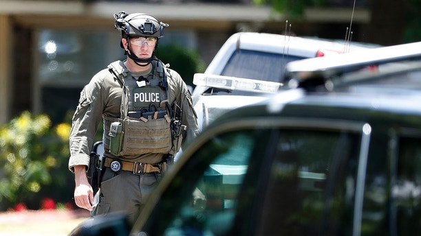 State and federal law enforcement officers in tactical gear work outside a home in Alvin, Texas, as part of the investigation in the aftermath of a deadly shooting at Santa Fe High School on Friday, May 18, 2018. (Kevin M. Cox /The Galveston County Daily News via AP)