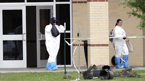Officials remove items from Santa Fe High School in Santa Fe, Texas, on Saturday, May 19, 2018. Students and teachers were allowed back to parts of the school to retrieve their belongings Saturday. A gunman opened fire inside the school Friday, May 18, 2018, killing several people. (AP Photo/David J. Phillip)