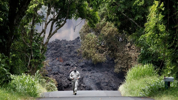 Lieutenant Colonel Charles Anthony, of the Hawaii National Guard, measures sulfur dioxide gas levels at a lava flow on Highway 137 southeast of Pahoa during ongoing eruptions of the Kilauea Volcano in Hawaii, U.S., May 20, 2018.  REUTERS/Terray Sylvester - RC123CF989A0