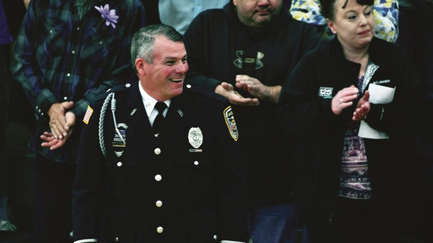 Mark Dallas, a school resource officer, reacts as he leads Dixon High School's Class of 2018 into their graduation ceremony in Lancaster Gymnasium at the school in Dixon, Ill., Sunday, May 20, 2018. Matthew A. Milby Jr., 19, is charged with firing shots inside of his northern Illinois high school Wednesday as seniors met for graduation rehearsal at the school before he was shot by Dallas. Milby was released from a hospital Thursday and transferred to the jail. (Peter Balser/The Telegraph via AP)