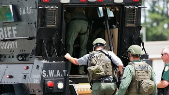 Bay County Sheriff's Office deputies enter an armored vehicle at the corner of 23rd Street and Beck Avenue, Tuesday, May 22, 2018, in Panama City, Fla., in response to an active shooter in the area. (Joshua Boucher/News Herald via AP)