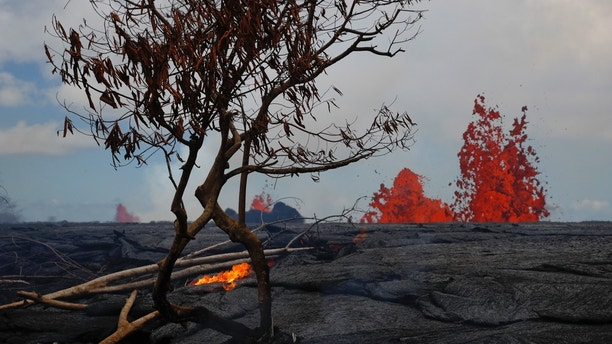 Lava erupts from fissures in the Leilani Estates subdivision near Pahoa, Hawaii, Tuesday, May 22, 2018. Authorities were racing Tuesday to close off production wells at a geothermal plant threatened by a lava flow from Kilauea volcano on Hawaii's Big Island. (AP Photo/Jae C. Hong)