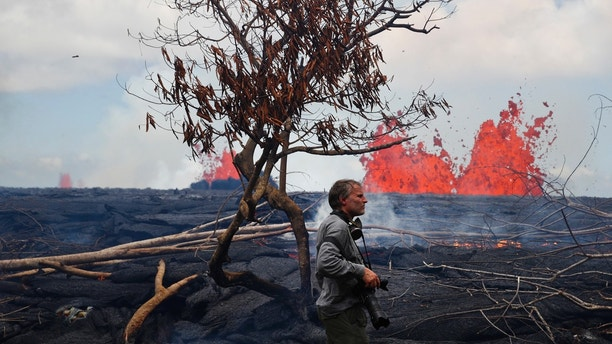 Photographer Carsten Peter, of Germany, watches lava erupt from fissures in the Leilani Estates subdivision near Pahoa, Hawaii, Tuesday, May 22, 2018. Authorities were racing Tuesday to close off production wells at a geothermal plant threatened by a lava flow from Kilauea volcano on Hawaii's Big Island. (AP Photo/Jae C. Hong)