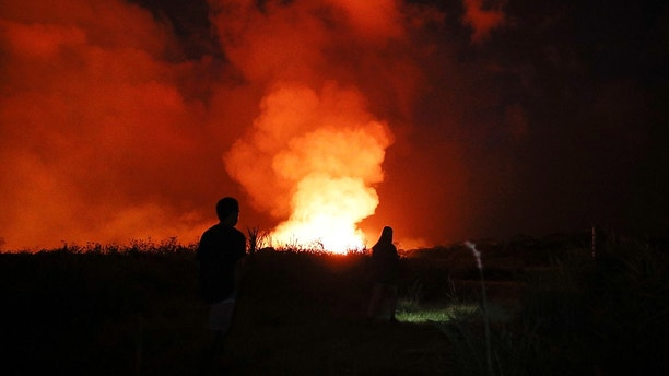 Two onlookers walk along a trail to watch lava erupt from a fissure in Kapoho, Hawaii Monday, May 21, 2018. The eruption of Kilauea volcano in Hawaii sparked new safety warnings about toxic gas on the Big Island's southern coastline after lava began flowing into the ocean and setting off a chemical reaction. (AP Photo/Jae C. Hong)