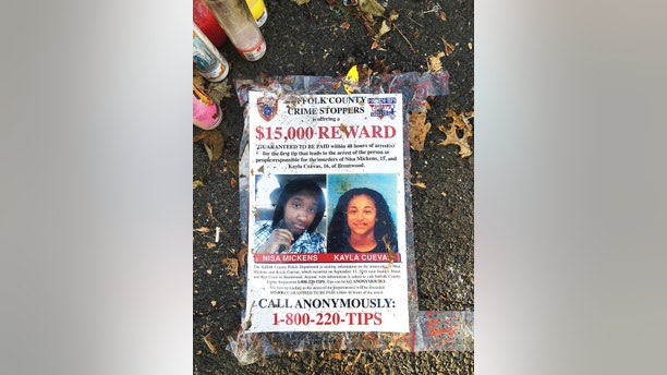 FILE - In this Sept. 27, 2016 file photo, a poster featuring photos of Nisa Mickens and Kayla Cuevas is part of a memorial near the spot where their bodies were found in Brentwood, N.Y. Mickens, 15, and Cuevas, 16, both students at Brentwood High School, were beaten and hacked to death by a carload of gang members who spotted them walking down the street. Investigators said Cuevas had been feuding verbally with gang members. President Donald Trump is scheduled travel to New York on Friday, July 28, to meet with law enforcement on Long Island and discuss the MS-13 street gang. (AP Photo/Claudia Torrens, File)