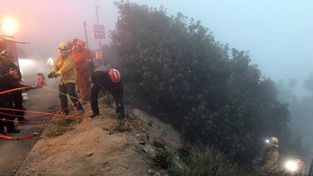 San Bernardino County firefighters rescue a woman whose car plunged over the side of Highway 18 near Crestline on May 24, 2018. (Courtesy of San Bernardino County Fire Department)