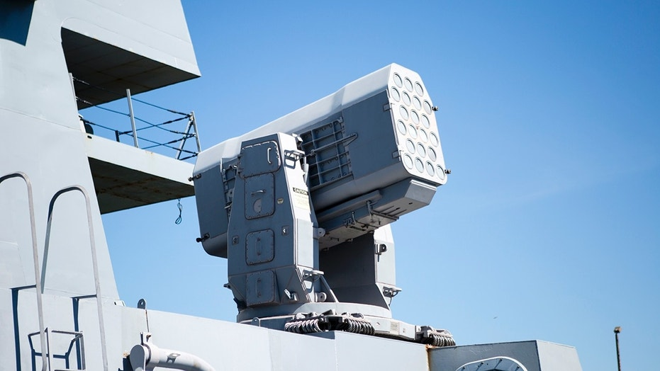 The ship is equipped with numerous missile launchers and guns for defense.