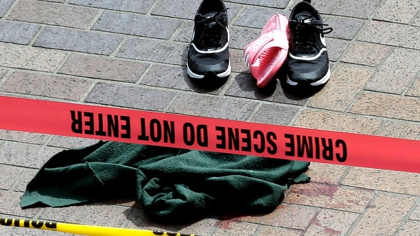 CORRECTS TO MOTORIST-Clothing is strewn on the sidewalk at a scene where pedestrians were hit by a motorist in Portland, Ore., Friday, May 25, 2018. Police say three women have been injured in a hit-and-run crash near Portland State University. (AP Photo/Don Ryan)