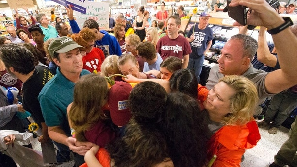"""Demonstrators do a group hug after a protest at a Publix Supermarket in Coral Springs, Fla., Friday, May 25, 2018. Students from the Florida high school where 17 people were shot and killed earlier this year did a """"die in"""" protest at a supermarket chain that backs a gubernatorial candidate allied with the National Rifle Association. Shortly before the the """"die-in"""" Publix announced that it will suspend political contributions. (AP Photo/Wilfredo Lee)"""