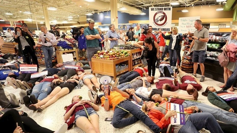 Demonstrators lie on the floor at a Publix Supermarket in Coral Springs, Fla., Friday, May 25, 2018.