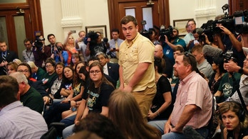 Tyler Morrison, student at Santa Fe High School, Texas, standing center, speaks during a roundtable discussion in Austin, Texas, Thursday, May 24, 2018, hosted by Texas Gov. Gregg Abbott to address safety and security at Texas schools in the wake of the shooting at Santa Fe. Thursday's roundtable included victims, students, families and educators from the Santa Fe, Alpine and Sutherland Springs communities. (AP Photo/Eric Gay)