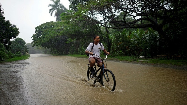 A man rides a bicycle down a flooded road as Subtropical Storm Alberto passes by the west coast of Cuba, in Bahia Honda, Cuba, May 26, 2018.  REUTERS/Alexandre Meneghini - RC1953FEA600
