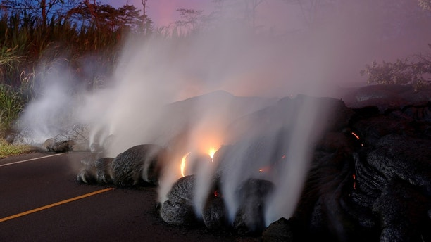 Volcanic gases rise from the Kilauea lava flow that crossed Pohoiki Road near Highway 132, near Pahoa, Hawaii, U.S., May 28, 2018. REUTERS/Marco Garcia - RC1D522D5A50