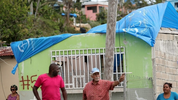 Residents stand near a house with a plastic sheet replacing the roof hit by Hurricane Maria in September, in a neighbourhood in Canovanas, Puerto Rico April 10, 2018.  REUTERS/Alvin Baez - RC13DE832FD0