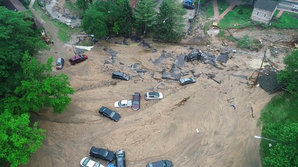 This image made from video provided by DroneBase shows vehicles swept by floodwater near the intersection of Ellicott Mills Drive and Main Street in Ellicott City, Md., Monday, May 28, 2018. Howard County Executive Allan Kittleman said Monday morning that his priorities are finding a missing man and assessing the condition of buildings that house shops, restaurants and families. (DroneBase via AP) Missing National Guardsman in Maryland was rescuing woman, cat during flash floods, report says Missing National Guardsman in Maryland was rescuing woman, cat during flash floods, report says 1527599636180