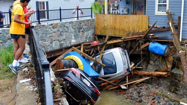 Residents gather by a bridge to look at cars left crumpled in one of the tributaries of the Patapsco River that burst its banks as it channeled through historic Main Street in Ellicott City, Md., Monday, May 28, 2018. Sunday's destructive flooding left the former mill town heartbroken as it had bounded back from another destructive storm less than two years ago. (AP Photo/David McFadden) Missing National Guardsman in Maryland was rescuing woman, cat during flash floods, report says Missing National Guardsman in Maryland was rescuing woman, cat during flash floods, report says 1527599791328