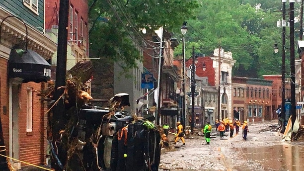 Rescue workers walk along the main street in Ellicott City, Md., Sunday, May 27, 2018. Sudden flash floods hit the city of Maryland Sunday, which had suffered similar devastation two years ago, turned into a raging river that reached the first floor of some buildings and swept away parked cars, authorities and witnesses say. (Libby Solomon / The Baltimore Sun via AP)
