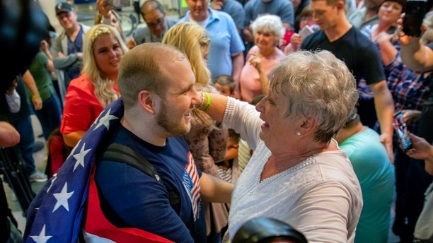 Josh Holt, left, is draped in an American flag by his grandmother Linda Holt upon returning to Salt Lake City on Monday, May 28, 2018, as he was freed this weekend after being held in a Venezuelan jail for nearly two years. He returned home to Salt Lake City on Monday night after getting medical care and visiting President Donald Trump in Washington. (AP Photo/Kim Raff)
