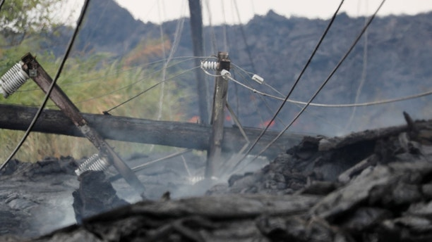 Utility poles and power lines sit destroyed in the Kilauea lava flow on Pohoiki Road near Pahoa, Hawaii, U.S., May 29, 2018.  REUTERS/Marco Garcia - RC1AF484E8F0