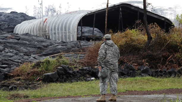 Maj. Jeff Hickman, of the Hawaii National Guard, stands near a structure destroyed by the Kilauea lava flow, in Leilani Estates near Pahoa, Hawaii, U.S., May 29, 2018.  REUTERS/Marco Garcia - RC1DFD73DCE0